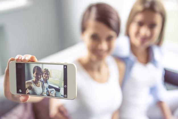 Dos hermosas chicas están haciendo selfie usando un teléfono inteligente.