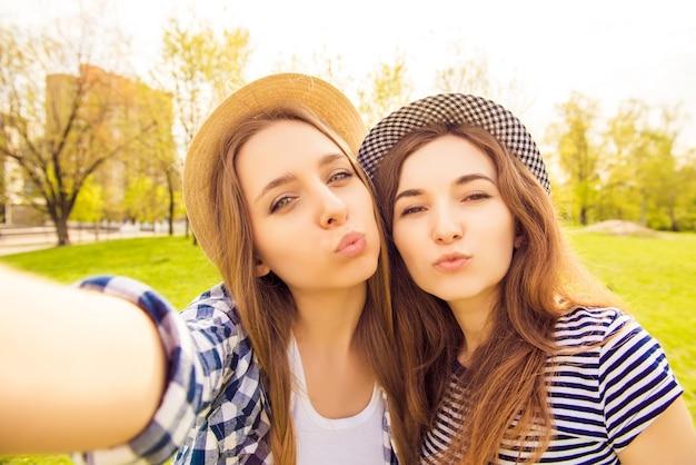 Dos hermosas chicas en gorras haciendo selfie y haciendo pucheros
