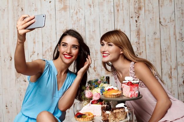 Dos hermosas chicas haciendo selfie en fiesta.