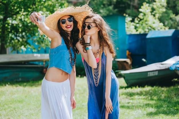 Dos hermosas chicas hippie para hacer selfie cerca de un barco viejo.