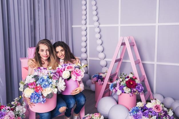 Dos hermosas chicas en jeans y suéter rosa con decoración de flores en cestas