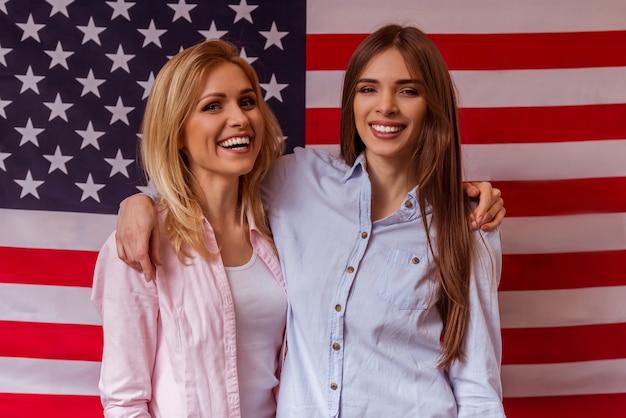 Dos hermosas chicas jóvenes están de pie contra la bandera americana