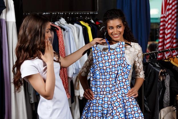 Dos hermosas chicas jóvenes haciendo compras en el centro comercial.