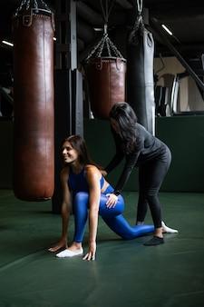 Dos hermosas chicas jóvenes haciendo fitness en un gimnasio. estirar los músculos de la espalda y las piernas.