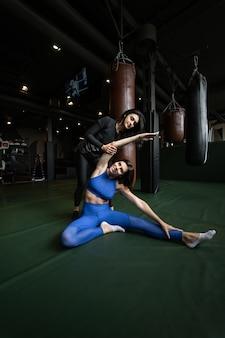 Dos hermosas chicas jóvenes haciendo fitness en un gimnasio. estirar los músculos de las piernas y los brazos.