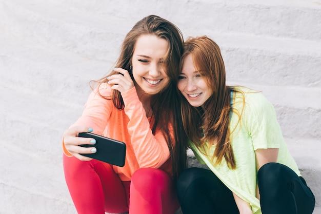 Dos hermosas chicas jóvenes sentadas en las escaleras, mirando el teléfono inteligente y riendo