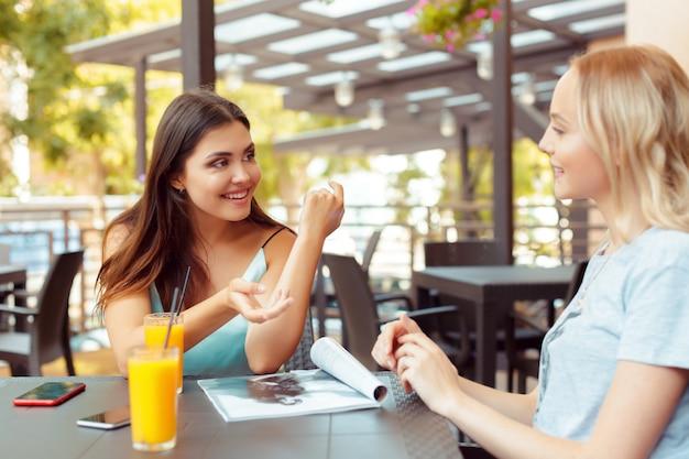 Dos hermosas chicas jóvenes sentadas junto a la mesa en el café