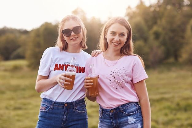 Dos hermosas chicas lindas se paran cerca una de la otra