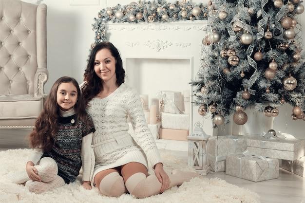 Dos hermosas chicas, madre e hija emplazamiento en un piso en navidad decoradas habitación.