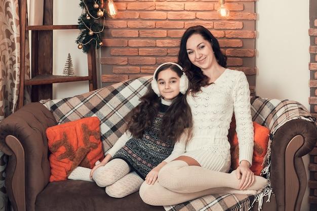 Dos hermosas chicas, madre e hija emplazamiento en un sofá en navidad decoradas habitación.