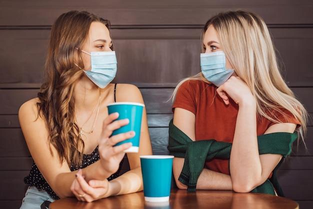 Dos hermosas chicas con máscaras en la cara pasan tiempo juntas tomando café y tomando té