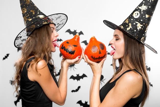 Dos hermosas chicas morenas con sombreros de bruja negros sostienen calabazas de halloween en sus manos y muestran sus lenguas.