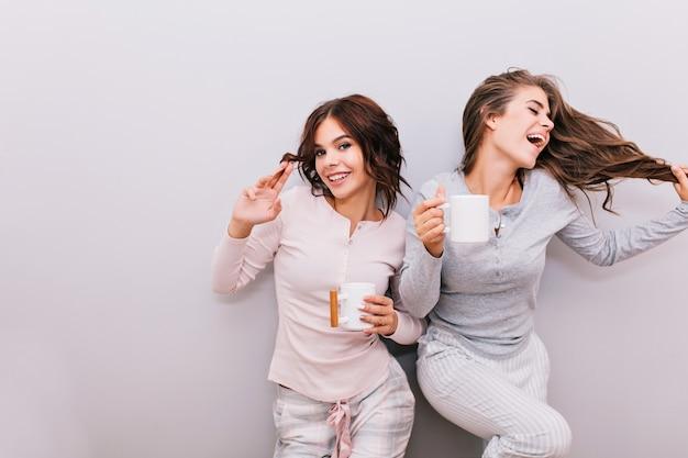 Dos hermosas chicas en pijama divirtiéndose en la pared gris. chica con pelo largo riendo y mantiene los ojos cerrados, otra con pelo rizado sonriendo.