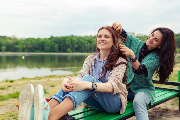 Dos hermosas chicas relajantes mientras hacen el peinado disfrutando del tiempo juntas