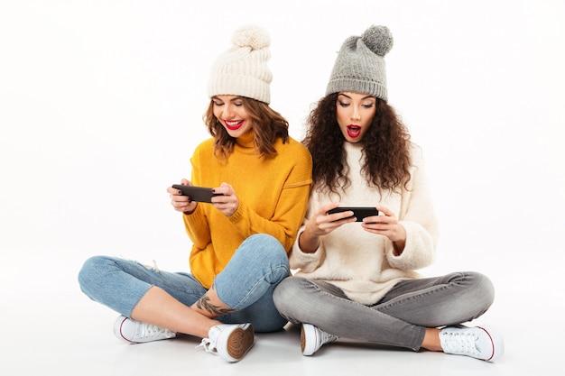 Dos hermosas chicas con suéteres y sombreros sentados juntos en el suelo mientras usan sus teléfonos inteligentes sobre la pared blanca