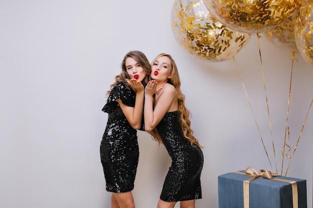Dos hermosas chicas en vestidos negros similares posando con expresión de cara de besos en la fiesta de cumpleaños. señora europea de pelo largo de pie junto a globos y regalos, enviando beso aéreo.