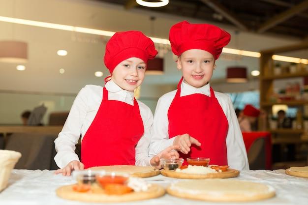Dos hermosas cocineras con camisas blancas y delantales rojos en el restaurante hacen pizza