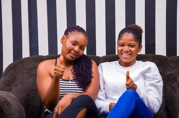 Dos hermosas damas africanas sonriendo como lo hicieron thumbs up