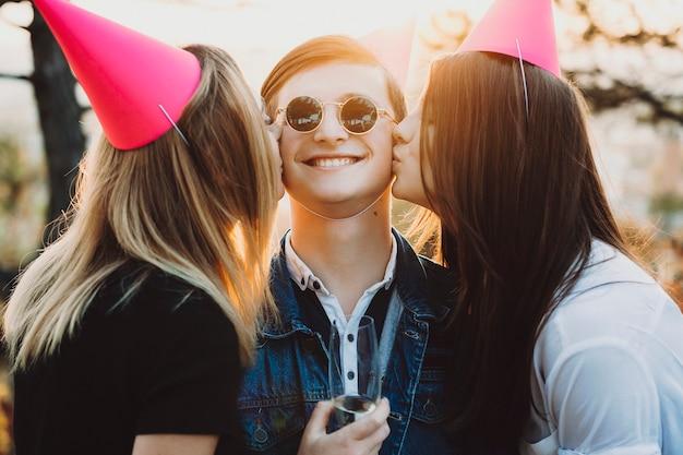 Dos hermosas damas besando al hombre sonriente con una copa de champán en las mejillas mientras tienen fiesta en un día soleado en la naturaleza