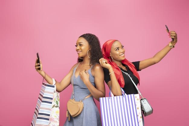 Dos hermosas damas con bolsas de la compra tomando autorretratos de pie espalda con espalda