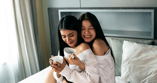Dos hermosas damas sentadas en la cama, bebiendo café juntas, con un sentimiento feliz. romántica pareja de amor, buena amistad.