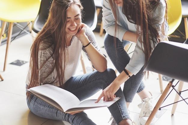 Dos hermosas gemelas pasan tiempo leyendo un libro en la biblioteca por la mañana. hermanas relajándose en un café y divirtiéndose juntas