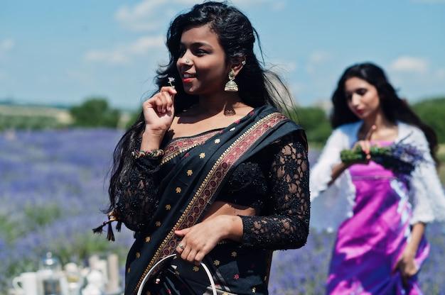 Dos hermosas girsl indias usan el vestido tradicional de la india sari en el campo de lavanda púrpura.