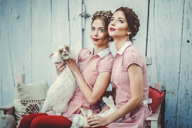 Dos hermosas hermanas gemelas se sientan con conejos