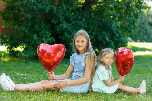 Dos hermosas hermanas en vestidos azules con globos en forma de corazón en la naturaleza