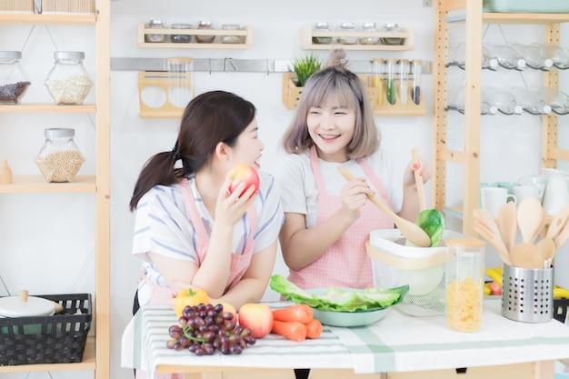 Dos hermosas y lindas mujeres tailandesas, dos mujeres asiáticas con un delantal rosa, hablan y se ayudan en la cocina.