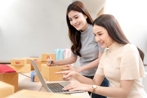 Dos hermosas mujeres asiáticas están comprobando los pedidos con ordenadores portátiles a través de internet. y empaque la caja de papel con una cara sonriente feliz, siendo un nuevo negocio en línea normal
