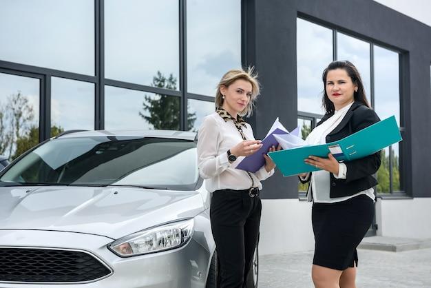 Dos hermosas mujeres con carpetas de colores posando junto al coche en la calle
