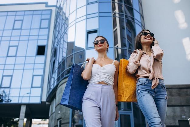 Dos hermosas mujeres de compras en la ciudad