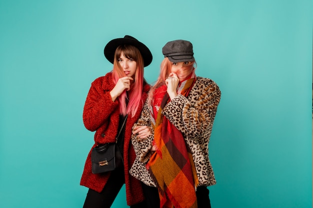 Dos hermosas mujeres con elegantes abrigos de piel sintética y bufanda de lana posando en la pared turquesa