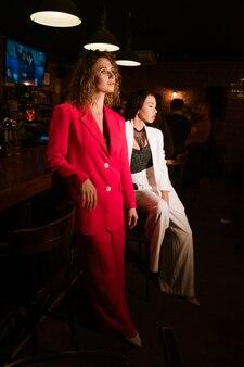 Dos hermosas mujeres de etnia caucásica en trajes elegantes y brillantes y maquillaje de noche en la noche