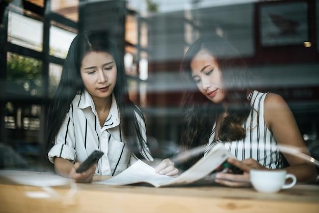 Dos hermosas mujeres hablando todo juntos en la cafetería cafetería