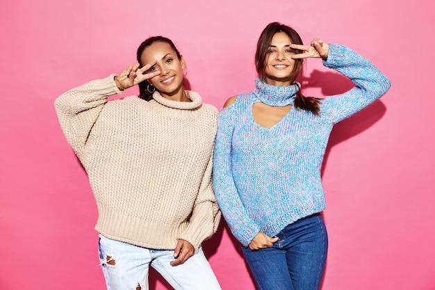 Dos hermosas mujeres hermosas sonrientes. mujeres de pie en elegantes suéteres blancos y azules, en la pared azul.