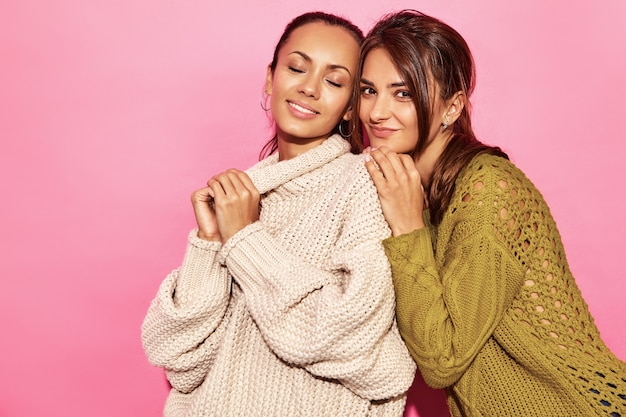 Dos hermosas mujeres hermosas sonrientes sexy. mujeres calientes de pie y abrazándose en elegantes suéteres blancos y verdes, en la pared de color rosa.