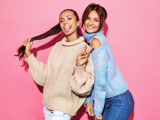 Dos hermosas mujeres hermosas sonrientes sexy. mujeres calientes de pie en elegantes suéteres blancos y azules, en la pared de color rosa. mostrando signo de paz
