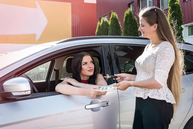 Dos hermosas mujeres intercambiando dólares y llaves del coche