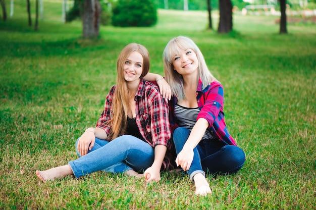 Dos hermosas mujeres jóvenes divirtiéndose al aire libre