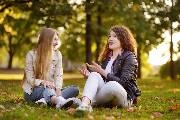 Dos hermosas mujeres jóvenes hablando mientras está sentado en el suelo en el parque soleado. comunicación y chismes.