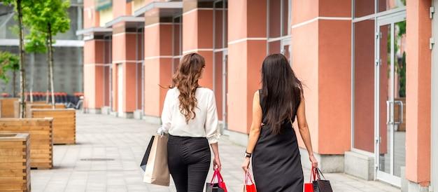 Dos hermosas mujeres jóvenes de moda caminando en el centro comercial con bolsas, vista posterior