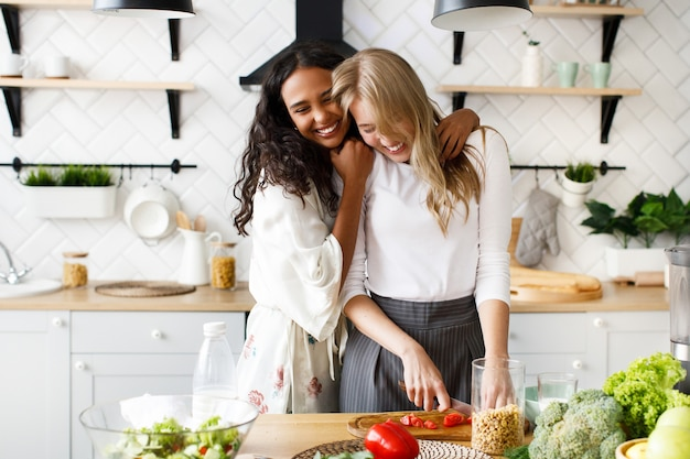 Dos hermosas mujeres jóvenes preparan un desayuno saludable y se abrazan cerca de la mesa llena de verduras frescas en la moderna cocina blanca