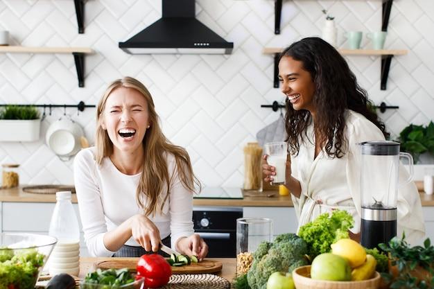 Dos hermosas mujeres jóvenes preparan un desayuno saludable y se ríen sinceramente cerca de la mesa llena de verduras frescas en la moderna cocina blanca.