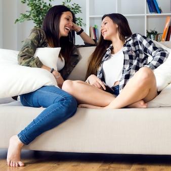 Dos hermosas mujeres jóvenes que se quedan en el sofá en casa.