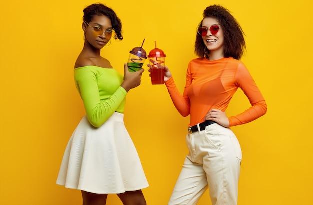 Dos hermosas mujeres jóvenes en ropa colorida de verano con cócteles