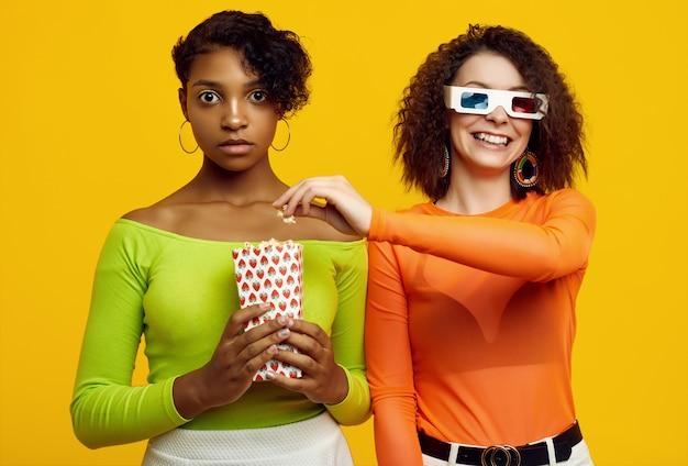 Dos hermosas mujeres jóvenes en ropa colorida de verano comiendo palomitas de maíz