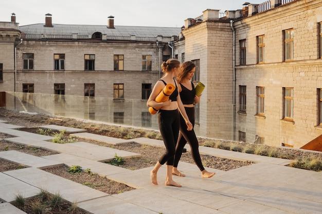 Dos hermosas mujeres jóvenes en ropa deportiva que van a hacer entrenamiento deportivo, gimnasia, yoga