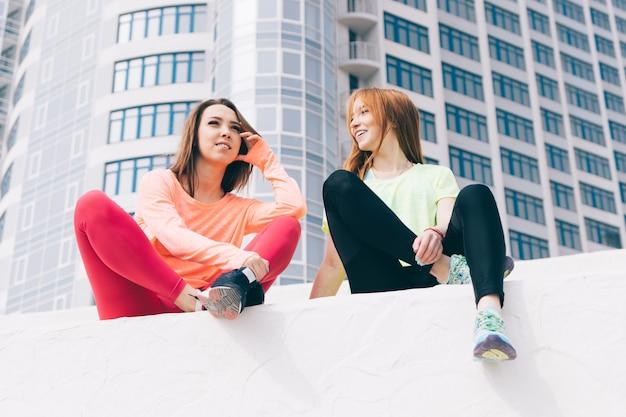 Dos hermosas mujeres jóvenes en ropa deportiva sentados y hablando en el fondo de edificios altos en la ciudad